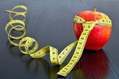 Red apple with measuring tape on board. Fruit as a healthy way of life. Weight reduction diet and workout Royalty Free Stock Photo