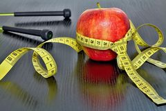 Red apple with measuring tape on board. Fruit as a healthy way of life. Weight reduction diet and workout Stock Photos