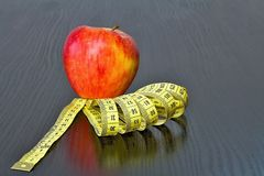 Red apple with measuring tape on board. Fruit as a healthy way of life. Weight reduction diet and workout Royalty Free Stock Photos