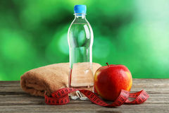 Red apple with measuring tape and bottle of water on grey wooden background. Stock Images