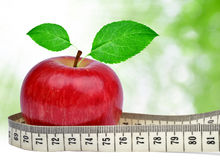 Red apple. With measuring tape on green background Stock Photos