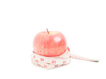 Red apple with measuring tape on isolated object on white backgr Royalty Free Stock Photo