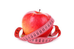 Red apple with measuring tape isolated on white. Stock Photo