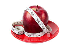 Red apple with measuring tape on red plate Stock Photography