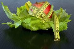 Red apple with measuring tape on a sheets of ice salad. Healthy eating brings attractive character curves Stock Photo