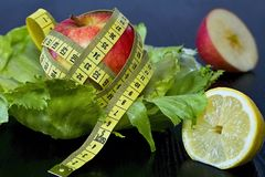 Red apple with measuring tape on a sheets of ice salad. Healthy eating brings attractive character curves Royalty Free Stock Image