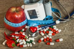 Red apple with measuring tape to measure length. Treatment of obesity and diabetes, measurement of blood pressure. Stock Photo
