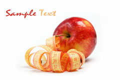 Red apple and measuring tape on a white. Royalty Free Stock Images