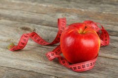 Red apple with measuring tape on wooden background Royalty Free Stock Photos