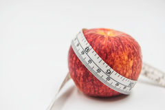 Red apple and Measuring tape wrapped around on white background Stock Photo