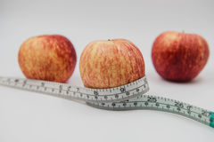 Red apple and Measuring tape wrapped around on white background Royalty Free Stock Photography