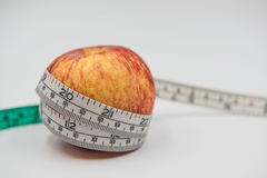 Red apple and Measuring tape wrapped around on white background Stock Image