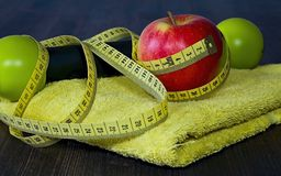 Red apple with measuring tape on a yellow towel. Equipments and fruits to maintain good fitness and optimum weight. Workout as a healthy way of life Stock Image