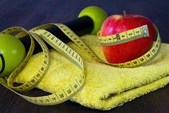 Red apple with measuring tape on a yellow towel. Equipments and fruits to maintain good fitness and optimum weight. Workout as a healthy way of life Stock Images