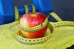 Red apple with measuring tape on a yellow towel. royalty free stock images