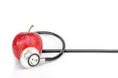 Red apple and Medical stethoscope on white background Royalty Free Stock Photography