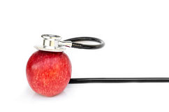 Red apple and Medical stethoscope on white background Royalty Free Stock Photo