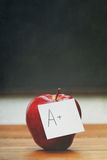 Red apple with note on desk with blackboard Royalty Free Stock Image