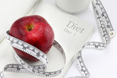 Red apple on a notebook and measuring tape Royalty Free Stock Images
