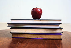 Red apple and  old books  on wooden table Stock Photo