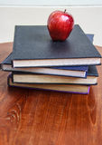 Red apple and  old books  on wooden table Stock Images