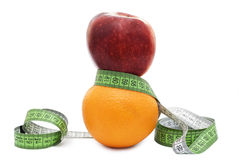 Red apple and orange with tape measure Royalty Free Stock Photos