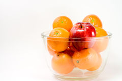 A Red Apple and Oranges in a Bowl Stock Image