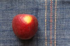 Red apple over blue cover Royalty Free Stock Image