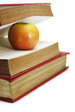 Red apple in between pages of old book. On white background Royalty Free Stock Photography