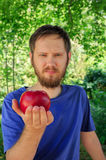 A red apple on the palm of young handsome man. Natural background Royalty Free Stock Image