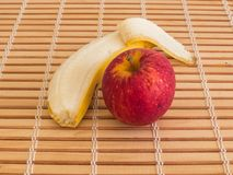 Red apple and peeled banana close up view. Healthy, fresh and tasty food, red apple and peeled banana in close-up view, on wooden table Stock Images