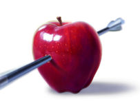 Red apple pierced by an arrow. On white background, with depth of field Stock Photos