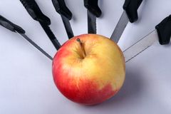 Red apple pierced with knives Stock Photo