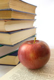 Red apple and pile of books. Photo close up Royalty Free Stock Photos