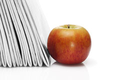 Red apple beside pile of school workbooks Stock Images