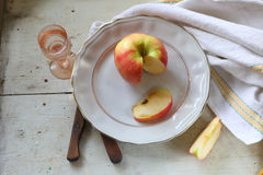 Red apple on a plate and vodka in a transparent wine-glass Royalty Free Stock Photography