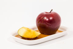 Red apple and red apple slice with drops of honey on white plate Royalty Free Stock Image