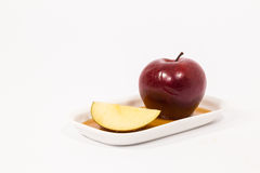 Red apple and red apple slice on white plate with honey isolated Stock Photos