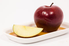 Red apple and red apple slice on white plate with honey isolated Royalty Free Stock Images