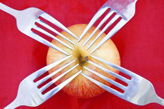 Red apple on red with four forks Royalty Free Stock Images
