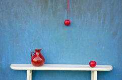 Red apple and red vase on white shelf Stock Photography