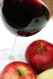 Red apple and red wine. Red wine in a glass with four apple Royalty Free Stock Image