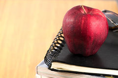 Red apple resting on the book  with glasses Royalty Free Stock Photo