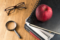 Red apple resting on the book  with glasses and magnifying glass Royalty Free Stock Photo