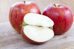 Red apple. Ripe apples on a wooden cutting board, one of the fruits is cut into half Royalty Free Stock Image