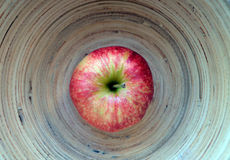 A red apple on the round bamboo background Royalty Free Stock Photography
