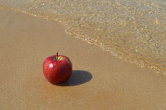 Red apple on the sandy beach Royalty Free Stock Photography