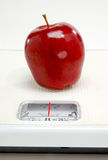 Red apple on scale Stock Photography