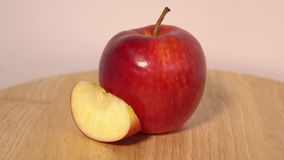 Red apple with slice on wooden table Royalty Free Stock Photos