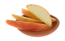 Red apple slices in a small clay bowl Stock Photo